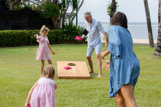 Happy family playing cornhole game by the sea on sunny summer day. Parents and children playing bean bag toss