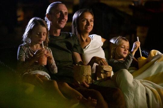 Happy family sitting on sofa enjoying movie night outdoor at home backyard together. Mother, father and children watching projector, TV, movies with popcorn in the evening