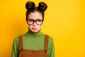 Photo of sad offended lady two funny buns geek nerd student failed examination crying unhappy tears grimacing wear specs green pullover brown overall isolated yellow color background