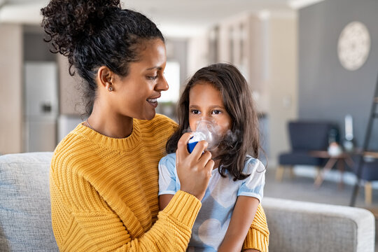 African mother helping child use nebulizer aerosol