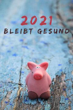 Rosa Glücksschwein auf blauem Holzhintergrund, mit Silvesterwünschen 2021 und Gesundheitswünschen, bleibt gesund.