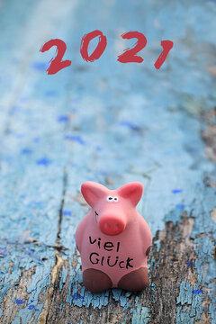 Rosa Glücksschwein auf blauem Holzhintergrund, wünscht viel Glück mit  Silvesterwünschen und Glückwünschen für das Jahr 2021.