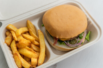 Cheeseburger with freshly made fries ordered for take away or to be delivered home