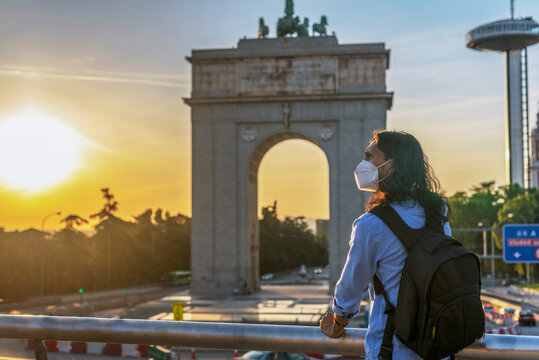 Young Hispanic male with a medical mask enjoying the beautiful view of a monument in Moncloa, Spain