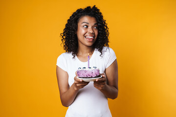 Image of happy african american woman holding birthday cake with candle