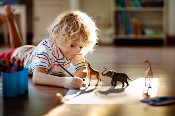 Little boy shadow drawing animals.