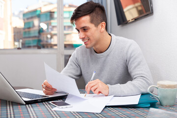 Young happy man sitting at home table working with papers, analyzing domestic budget. High quality photo