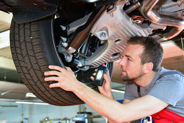 Auto mechanic repairs vehicle in a workshop - checking brakes for safety