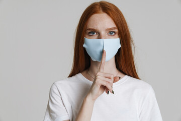 Image of young ginger girl in face mask showing silence gesture