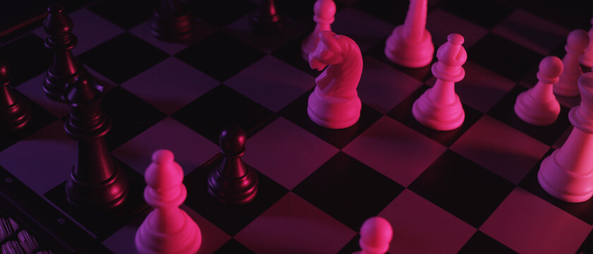 Chess pieces on a chessboard in a colorful fashion style. Studio neon light footage. Pink and purple colors. Fashion, business concept. Depth of field, soft focus