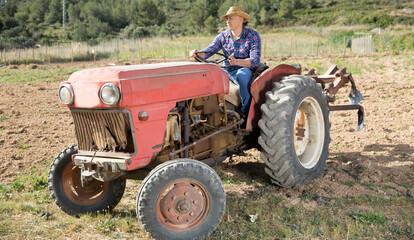 Positive man working on farm tractor. High quality photo