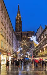 Strasbourg, France. Rue Merciere street with festive Christmas illumination, leading to Strasbourg Cathedral in twilight.