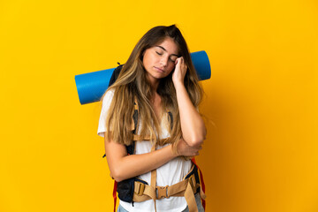 Young mountaineer woman with a big backpack isolated on yellow background with headache Papier Peint