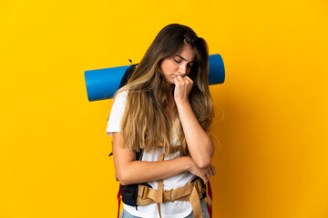 Young mountaineer woman with a big backpack isolated on yellow background having doubts Papier Peint