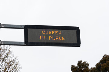 An overhead street sign showing the information of the curfew in place in the city of Melbourne, Australia during the COVID pandemic