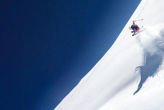 Jumping on skis through steep snow terrain