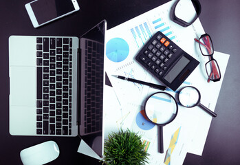 Top view,Business desk with a notebook, report graph chart, pen and tablet on wooden table