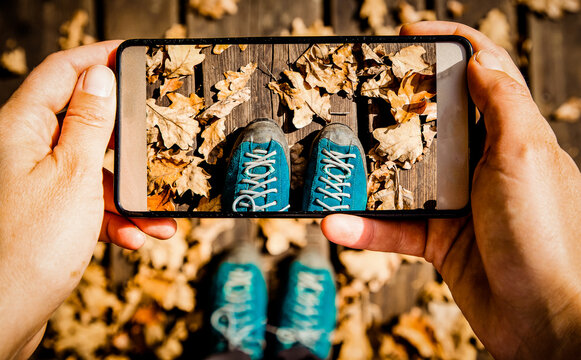 instagrammer taking a picture of her trekking shoes and fall foliage