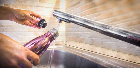 hand with aluminum eco friendly bottle pour tap water from the sink to reduce plastic usage