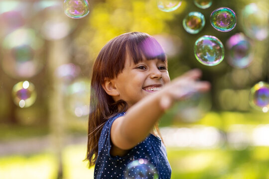 Girl playing with soap bubbles outdoors