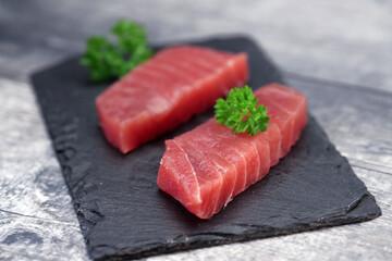 Raw tuna fillet on a black stone background