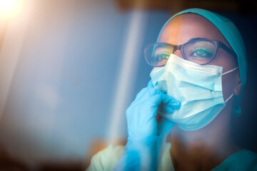 Young female medic, wearing a mask and glasses