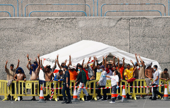 A group of immigrants is seen protesting in the port of Arguineguin, after dozens of migrants arrived in the southern part of the island of Gran Canaria