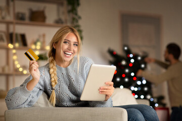 Excited lady shopping online on Christmas, using digital tablet