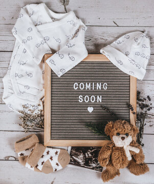 Coming soon sign. Baby announcement sign on a rustic white background. Coming soon concept.