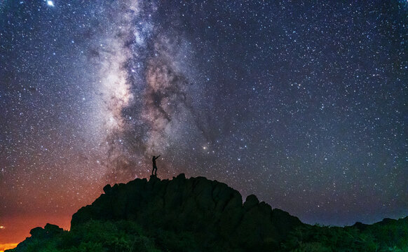 Silhouette of a young man under the stars looking at the lactea way of the Caldera de Taburiente near the Roque de los Muchahos on the island of La Palma, Canary Islands. Spain, astrophotography
