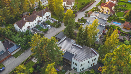 Top drone view of private sector of modern city. Luxury architecture. Road and houses. Green trees.