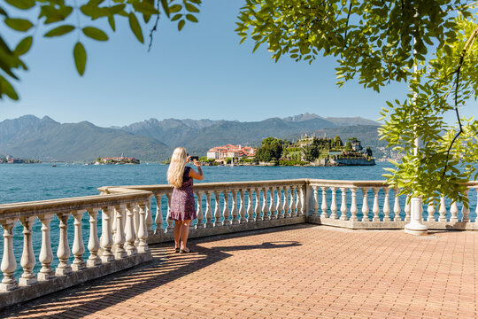 Mid adult female tourist photographing view of Isola Bella, Stesa, Italy