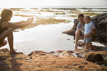 Mother taking photograph of father and son, on beach