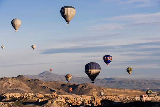 Hot air balloons floating over rock formations at sunrise in the Red Valley, Goreme National Park, Cappadocia, Anatolia, Turkey