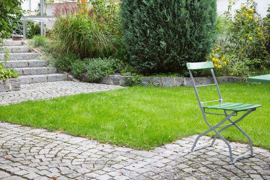 Terrassenförmige Gartengestaltung eines Hanggrundstücks: Über Treppe und Gehweg aus Natursteinen verbundene Terrassen mit Gartenmöbeln und Mauern mit Gräsern, Blumen und Konifere bepflanzt
