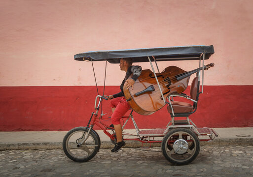 Man carrying double bass on tricycle in colonial street, Trinidad de Cuba