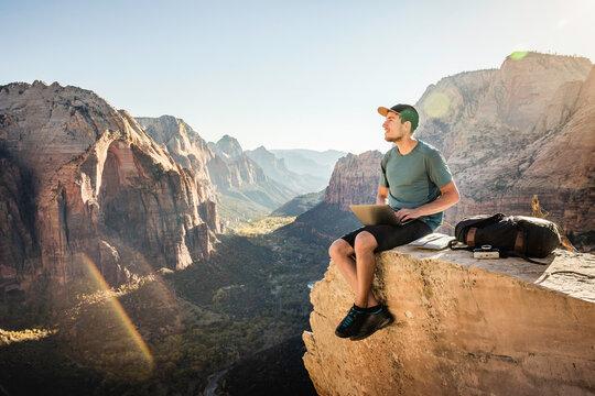 Man hiking Angels landing trail, sitting on rock, using laptop, Zion National Park, Utah, USA