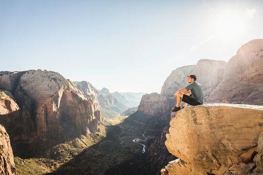 Man hiking Angels landing trail, sitting on rock, Zion National Park, Utah, USA