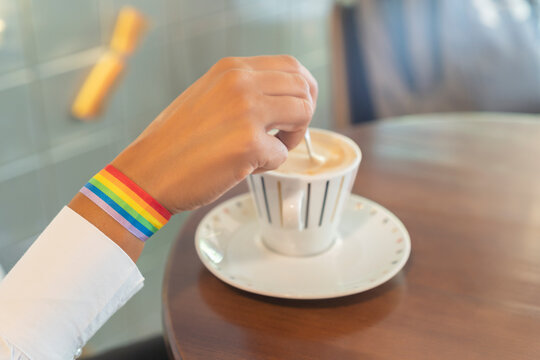 woman's hand with lgtbi bracelet with cup of coffee