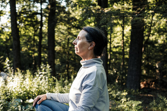 Side view of senior woman meditating outdoors
