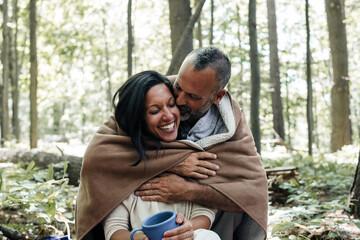Smiling man kissing his partner at campsite