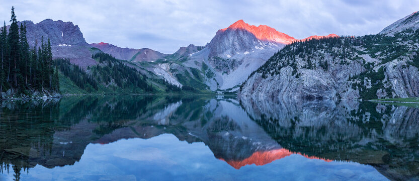 Snowmass Peak reflecting in Snowmass Lake during sunrise