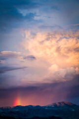 View of storm clouds with rainbow over mountain