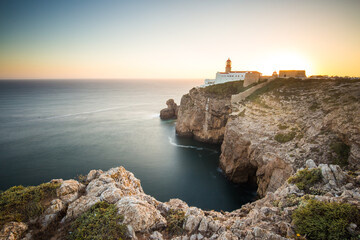 View of lighthouse on rocky coastline by sea