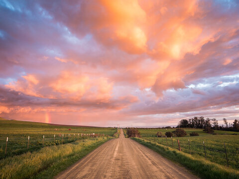View of dirt road passing through fields during sunset