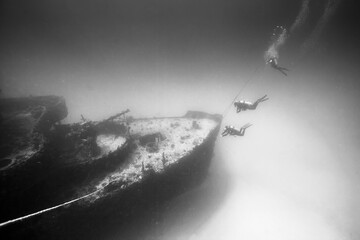 Divers exploring ship wreck undersea