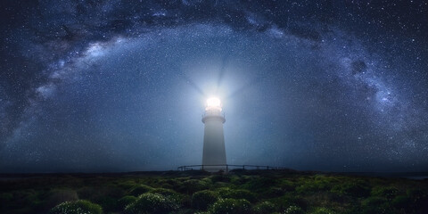 View of lighthouse against milky way at night