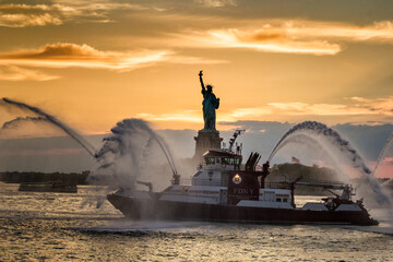 Fire Department vessel spraying water during sunset