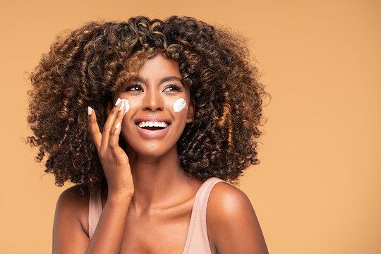 Beautiful african girl applying a cream on cheek.