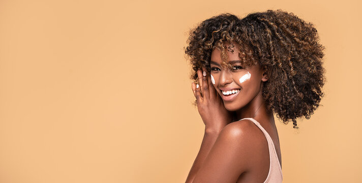 Young afro woman with moisturizer on face.
